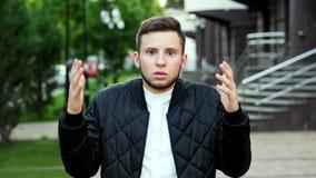 Hombre hermoso joven que expresa el asombro y la admiración en la calle Retrato del primer metrajes