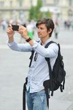 Hombre hermoso joven que fotografía con el teléfono elegante móvil Fotos de archivo libres de regalías