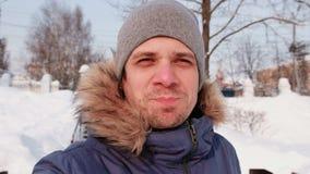 Hombre hermoso joven que habla en la conexión video y que camina en parque de la ciudad del invierno en día nevoso con nieve que  almacen de metraje de vídeo