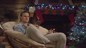 Hombre hermoso joven que hace compras en línea usando tarjeta del smartphone y de crédito en noche de la Navidad almacen de metraje de vídeo