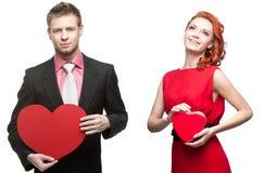 Hombre hermoso joven que lleva a cabo el corazón rojo y mujer alegre en blanco Imagen de archivo libre de regalías