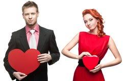Hombre hermoso joven que lleva a cabo el corazón rojo y mujer alegre en blanco Foto de archivo