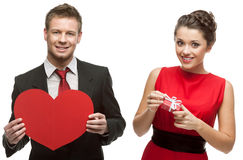 Hombre hermoso joven que lleva a cabo el corazón rojo y mujer sonriente que lleva a cabo g Fotografía de archivo