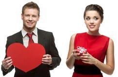 Hombre hermoso joven que lleva a cabo el corazón rojo y mujer sonriente que lleva a cabo g Imagenes de archivo
