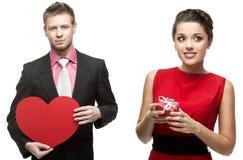 Hombre hermoso joven que lleva a cabo el corazón rojo y mujer sonriente que lleva a cabo g Imágenes de archivo libres de regalías