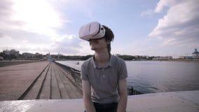Hombre hermoso joven que lleva gafas de la realidad virtual en una ciudad almacen de video
