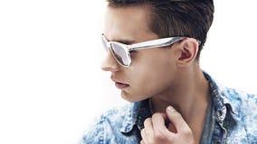 Hombre hermoso joven que lleva las gafas de sol elegantes Imagen de archivo