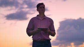 Hombre hermoso joven que mecanografía en la tableta y que mira alrededor, cielo rosado hermoso en fondo metrajes