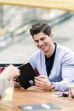 Hombre hermoso joven que mira el menú foto de archivo