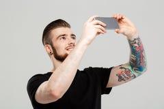 Hombre hermoso joven que mira el teléfono sobre fondo gris imagen de archivo libre de regalías
