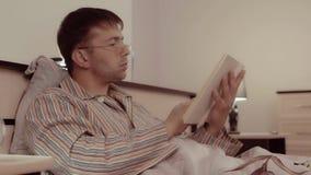Hombre hermoso joven que mira a través de su libro antes de ir a dormir metrajes