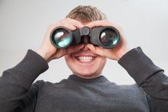 Hombre hermoso joven que mira a través de ventana con los vidrios binoculares Imagen de archivo
