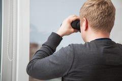 Hombre hermoso joven que mira a través de ventana con los vidrios binoculares Fotos de archivo libres de regalías