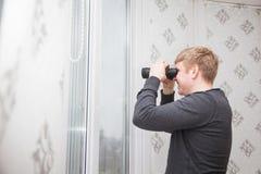 Hombre hermoso joven que mira a través de ventana con los vidrios binoculares Imagen de archivo libre de regalías