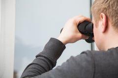 Hombre hermoso joven que mira a través de ventana con los vidrios binoculares Foto de archivo libre de regalías