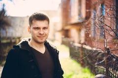 Hombre hermoso joven que permanece cerca de casa de madera vieja en otoño o el SP Imágenes de archivo libres de regalías