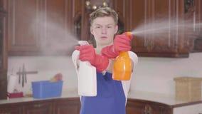 Hombre hermoso joven que pone las botellas de detergente a la cámara y a los esprayes él que imita tiros del arma D?a de la limpi metrajes