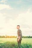 Hombre hermoso joven que se coloca en campo verde Fotografía de archivo libre de regalías