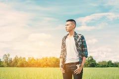 Hombre hermoso joven que se coloca en campo verde Fotos de archivo libres de regalías