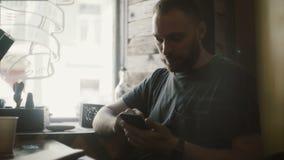 Hombre hermoso joven que se sienta en café, café de consumición y sosteniendo el smartphone, usando la tecnología inalámbrica almacen de video