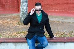 Hombre hermoso joven que se sienta en el banco en llevar negro de la capa Imágenes de archivo libres de regalías