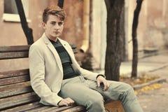 Hombre hermoso joven que se sienta en un banco Imagenes de archivo
