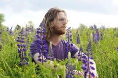 Hombre hermoso joven que se sienta en un campo de flor Fotos de archivo