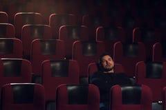 Hombre hermoso joven que se sienta solamente en teatro del cine Foto de archivo libre de regalías