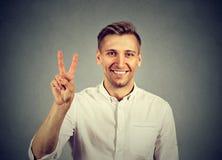 Hombre hermoso joven que soporta la victoria de la paz, muestra dos Foto de archivo libre de regalías