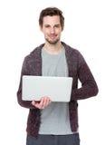 Hombre hermoso joven que trabaja con el ordenador portátil Foto de archivo libre de regalías