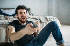 Hombre hermoso joven que ve la TV en un piso en casa fotos de archivo libres de regalías