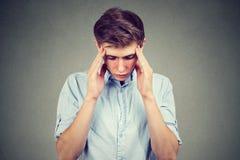 Hombre hermoso joven triste con la expresión subrayada preocupante de la cara que mira abajo Fotos de archivo