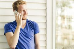 Hombre hermoso pelirrojo feliz que usa el teléfono y la sonrisa Imagen de archivo libre de regalías