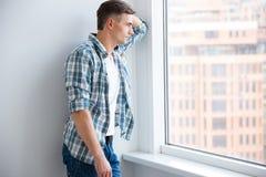 Hombre hermoso pensativo que se coloca cerca de la ventana Imagen de archivo