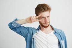 Hombre hermoso positivo joven en auriculares que escucha el baile de la música que muestra paz sobre el fondo blanco Imagenes de archivo