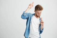 Hombre hermoso positivo joven en auriculares que escucha el baile de la música que se mueve sobre el fondo blanco Fotos de archivo libres de regalías