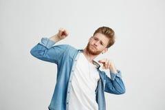 Hombre hermoso positivo joven en auriculares que escucha el baile de la música que se mueve sobre el fondo blanco Imagen de archivo libre de regalías