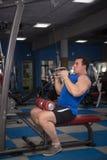 Hombre hermoso, potente, fuerte que presenta en el gimnasio Fotografía de archivo libre de regalías