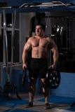 Hombre hermoso, potente, fuerte que presenta en el gimnasio Foto de archivo libre de regalías