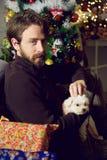 Hombre hermoso que acaricia noche de la Navidad del pequeño perro al lado de árbol en casa Imagenes de archivo