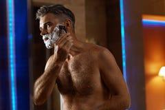 Hombre hermoso que afeita la cara en cuarto de baño Preparación del pelo facial Fotografía de archivo