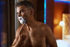 Hombre hermoso que afeita la cara en cuarto de baño Preparación del pelo facial Imágenes de archivo libres de regalías