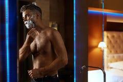 Hombre hermoso que afeita la cara en cuarto de baño Preparación del pelo facial Imagen de archivo libre de regalías
