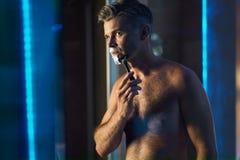 Hombre hermoso que afeita la cara en cuarto de baño Preparación del pelo facial Foto de archivo libre de regalías