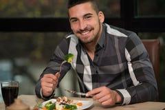 Hombre hermoso que almuerza en un restaurante Foto de archivo