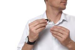 Hombre hermoso que aplica perfume en cuello contra el fondo blanco imagenes de archivo