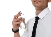 Hombre hermoso que aplica perfume en cuello contra el fondo blanco imágenes de archivo libres de regalías