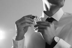 Hombre hermoso que aplica perfume en cuello contra fondo ligero Efecto blanco y negro imagenes de archivo