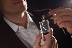 Hombre hermoso que aplica perfume en el cuello, primer fotos de archivo libres de regalías