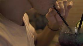 Hombre hermoso que bebe el cóctel alcohólico de la paja en el contador de la barra en la igualación del pub Cierre encima del cóc metrajes
